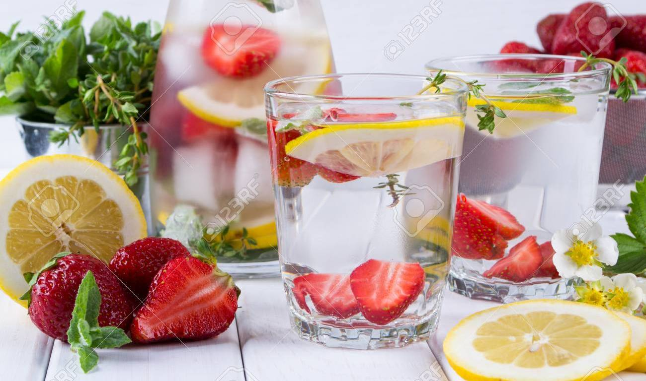 infused water glass pitcher two glasses strawberries lemon slices