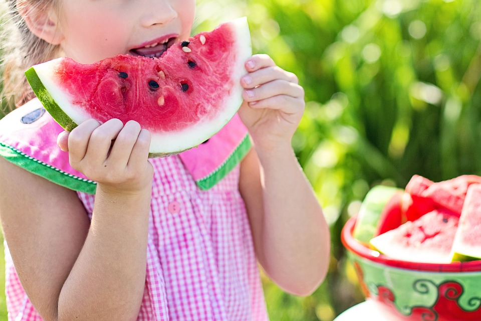 girl in pink dress biting into watermelon slice held in both hands