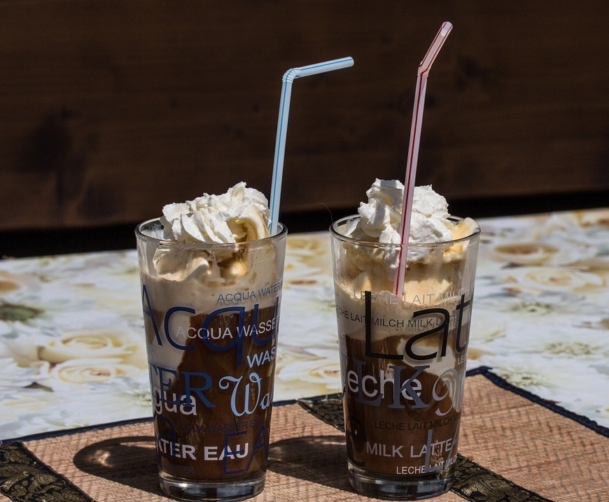 two glasses cold coffee whipped cream topping strawa