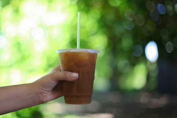 hand holding iced coffee takeaway glass drinking straw