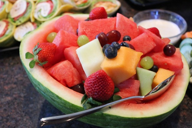 salad bowl made of empty half watermelon containing mixed fruit salad and a spoon