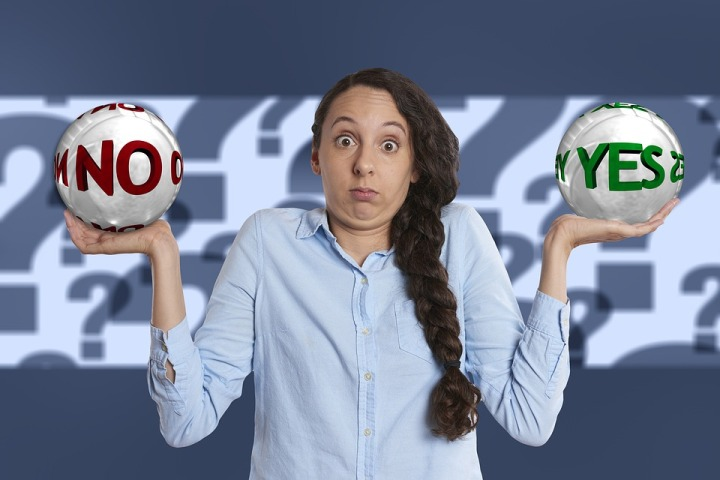 girl weighing yes and no in either hand indicatting decision fatigue