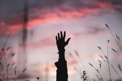 hand raised background sunset