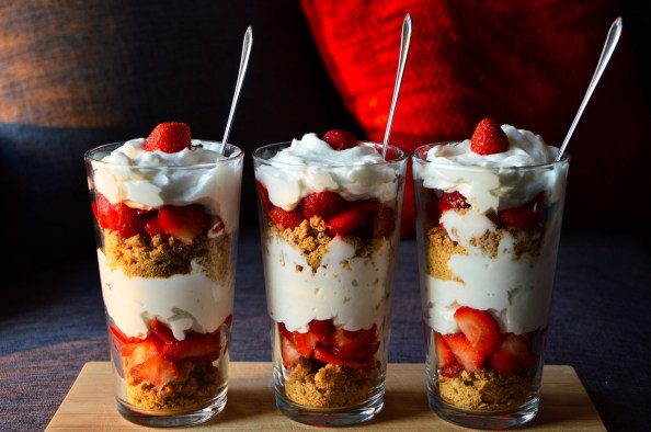 3 ice cream sundaes with alternating layers of chocolate ice cream whipped cream and strawberries