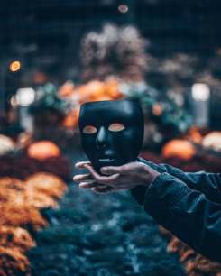 halloween and horror stories person holding black mask