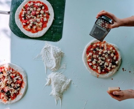 sprinkle toppings on three pizzas
