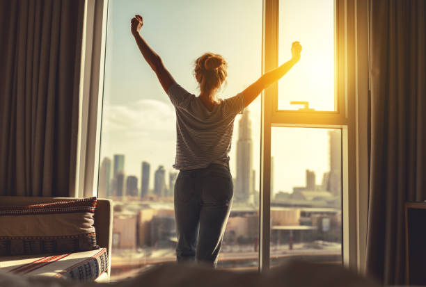waking up with enthusiasm woman stretching window
