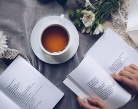white teacup person reading two books