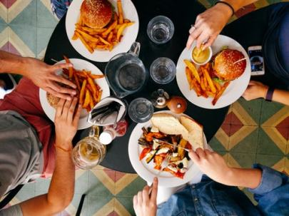 four persons eating on black wooden table