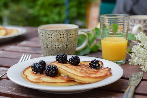 blacberries pancakes orange juice coffee cup wooden table