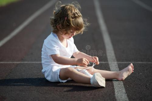 child in white tying shoelace