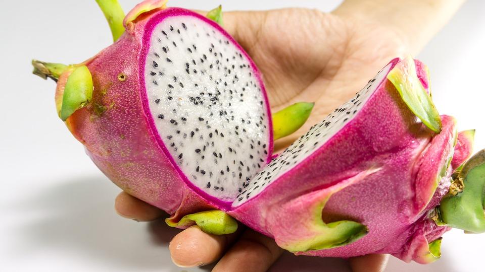 dragon fruit cut in half held in hand
