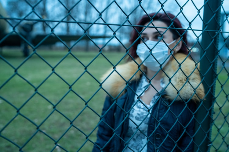 girl with mask in front of fence