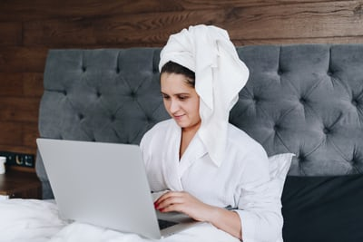 woman in white robe with laptop