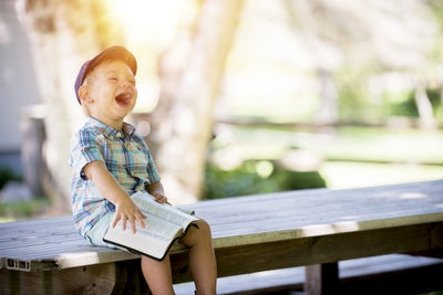 boy laughing book bench